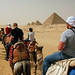 Study abroad program - students riding camels into the desert with the pyramid of Menkaure in the distance - Giza, Egypt