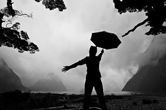 Dancing In The Rain, Milford Sound, New Zealand, In Black and White (Eloise Claire) Tags: newzealand blackandwhite bw selfportrait tree rain clouds umbrella self landscape person mood nz hood southisland fjord milfordsound southland fiordlandnationalpark sandflypoint piopiotahi