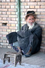 Portrait Ethnic Uyghuyr Grey Beard Man Wearing Traditional Quilted Coat Seated on Street Pavement Xinjiang Province China (eriagn) Tags: china street travel portrait people man face canon photography eos asia pavement culture documentary social elderly elder editorial xinjiang silkroad weathered uyghur greybeard bearded woodenstool revered quiltedcoat xinjiangprovince eriagn ngairelawson farwestchina ngairehart