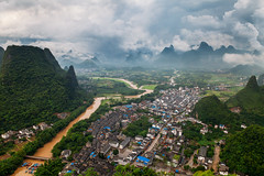 Overlooking Xingping (peter stewart photography) Tags: china travel cliff mountain tourism trekking river point landscape outdoors li daylight town high village cloudy yangshuo chinese stormy climbing shen peaks karst vantage xingping
