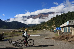 Mountain biking through small village on a Multi sport treking Mountain biking rafting kayaking trip in Nepal