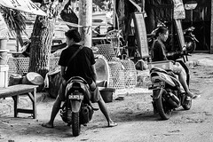 Look Both Ways (Pauls-Pictures) Tags: street two people urban blackandwhite bali woman man bike indonesia lens photography couple image candid portait pair sony streetphotography bodylanguage 7 scooter shy motorbike motor alpha coy 18200 photograhy streetphotos nex streetphotograhy streetpictures pedangbai sonynex7 sonyalphanex7 alphasonynex7