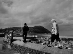 Big kids (adam_moralee) Tags: street sea bw white man black male men adam beach monochrome wall clouds dark walking landscape blackwhite hoodie seaside rocks wb explore devon hoody lucky finepix fujifilm minehead s1500 moralee adammoralee