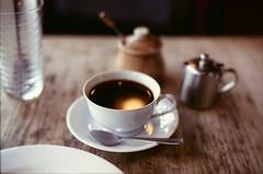 a cup of coffee (yocca) Tags: reflection film topf25 coffee table 50mm cafe nikon kyoto fuji dof bokeh f14 100v10f 300views f3 nikkor 2012 1000views xtra400 jan2012