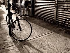 Broome St. Bike (crop) (sjnnyny) Tags: bicycle metal lowereastside streetphoto f71 sidwalk peopleonthestreet broomestreet nylife urbanstilllife stevenj riotgates sjnnyny k3ii hdpentaxda2040mmf284edlimiteddcwrlens 1200iso8001ec21mm