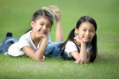 Two little asian girls laying on the green grass (Patrick Foto ;)) Tags: park family friends summer two portrait people playing cute green nature girl beautiful face field grass childhood smiling kids female laughing garden children asian fun outside happy spring healthy toddler funny pretty child friendship little outdoor sister background joy young relaxing meadow lifestyle happiness together daycare concept cheerful lying laying