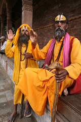 Two Sadhu Holy Men in Orange Saffron robes Kathmandu Nepal (eriagn) Tags: travel pink nepal orange man men canon beard religious eos beads asia peace documentary holy walkingstick kathmandu spiritual seated saffron robes travelphotography sahu duckbilled eriagn