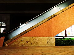 The Escalation of Unmet Expectations (Isabelle de Touchet) Tags: california light urban brown brick texture up lines wall architecture night stairs canon mall concrete rust outdoor geometry terracotta escalator angles nopeople surface fashionisland newportbeach stairwell diagonal socal limestone orangecounty stucco ocher burntsienna powershotsx50