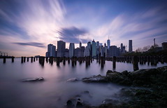 Skyline of New York City (roken-roliko) Tags: city nyc newyorkcity longexposure travel sunset sky usa newyork skyline architecture clouds america buildings reflections river rocks cityscape fineart towers nopeople nycskyline emptyspace buildingexterior traveldestination withoutpeople architectureexterior cityandarchitecture rolandshainidze