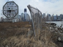 Long retired, the Colgate Clock in Jersey City sits in a weedy field by the Morris Canal. Life goes on in Lower Manhattan on a dreary winter day as the World Trade Center grows taller. Feb 2012. (wavz13) Tags: abandoned forgotten urbanruins bleak hudsonriver desolate abandonment batteryparkcity depressing oldclock forgottenplaces urbanwasteland newworldtradecenter vintageclock urbandesolation oldclocks oldpiers jerseycitywaterfront vintageclocks weedylot lostspaces jerseycityruins