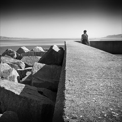 Looking Out to Sea (Petur) Tags: sea bw woman blancoynegro stone concrete blackwhite rocks mud breakwater
