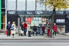 Bus stops. by Simas Lin - Bus stops is a study of strangers' sociability. Idea for this project was born in a very spontaneous way. I was waiting at a red traffic light and watching people at the bus stop. At least 40 people were at the stop and majority of them were looking into the bus coming direction. Immediately after seeing this scene an idea popped in my head – it would be great if I could make them all look at my camera! When I started analyzing the scene, asking myself why this affected me, I interpreted mass looking at the same direction as an expression of need to get out of socially uncomfortable space, a group of strangers. A human, by nature, is a sociable creature that needs any kind of interaction with other humans and what I saw at the stop was totally different. It inspired me to highlight the sociability of unfamiliar people. What you see is an unstaged group portraits of strangers made at public bus stops of Vilnius.  2015 - 2016 / Pt. 1.  www.simaslin.com