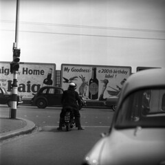 0511059 08 (ndpa / s. lundeen, archivist) Tags: street city england people blackandwhite bw man london english cars 6x6 tlr monochrome mediumformat blackwhite europe traffic nick helmet may citylife streetlife billboard motorbike 1950s motorcycle billboards intersection stoplight guiness rider sliceoflife 1959 dewolf triptoeurope nickdewolf photographbynickdewolf