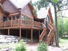 Log Home n the Lake (North Twin Builders) Tags: new wood trees windows brown house lake tree green home window glass rock pine architecture design log construction cabin doors arch exterior landscaping timber shingles rustic peak beam deck cedar eagleriver railing upnorth siding sconce custom posts doormat railings contractor wi lightfixture sunroom gable builder northwoods retainingwall shakes grills gutters doublehung customhome northernwi lakehome schrubs stairsw custombuilder lograiling northtwinbuilders