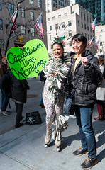 Money Bunny - 2 (UrbanphotoZ) Tags: nyc newyorkcity ny newyork man money smiling lashes manhattan feathers smiles rockefellercenter posing midtown lipstick rabbitears bodysuit fifthave easterparade passersby blackcoat moneybunny capitalismisntworking