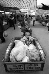 China - Qinghai (luca marella) Tags: travel people bw white black film blackwhite luca child market pb bn e cart bianco nero cina analogic qinghai golmud marella bikecart marellaluca