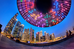 Invaders (Scintt) Tags: city travel sky urban distortion tourism architecture modern night clouds marina buildings lights evening bay hall flying twilight singapore glow place dusk centre alien curves surreal ufo fisheye cbd 8mm financial invasion circular saucer offices raffles samyang scintillation ilight scintt
