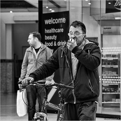 The ticket whisperer (John Riper) Tags: street uk england bw food white man black men monochrome beauty station bike bicycle liverpool canon john square photography mono glasses boots drink zwartwit candid ticket piercing l welcome healthcare limestreet 6d limestreetstation 24105 straatfotografie riper johnriper