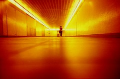 Solar subway (fotobes) Tags: red orange woman london lines station yellow lady reflections bag underground walking person lights solar vanishingpoint lca candid angles tunnel kingscross walkingaway lowdown sparse leadinglines redscale ratseye chinscraper lomographyredscalexr fotobes tunnelphilia