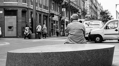 Waiting alone (Go-tea 郭天) Tags: street old people urban bw white man black cars rock canon bench outside eos 50mm blackwhite back seat coat pedestrians toulouse stress bnw shoppers bold 100d weating