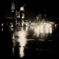 Rainy Sydney nights No. 1 (Albion 'a whole lotta busy' Harrison-Naish) Tags: light people urban blackandwhite bw building wet monochrome sepia night vintage dark square blackwhite sydney australia squareformat nsw cbd bnw timeless iphone rainynights johnslens iphoneography hipstamatic blackeyssupergrainfilm streetphotogoraphy
