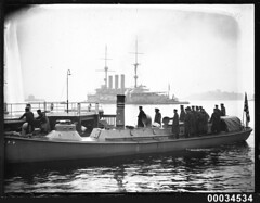 Japanese sailors standing on board a steam pinnace with HIJMS IZUMO in the background