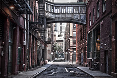 The Crossing (michaelelliottnyc) Tags: road street old city nyc newyorkcity bridge windows urban signs newyork tree brick abandoned glass stone architecture composition canon buildings lights wire alley iron path decay manhattan empty pipes streetscene historic cobblestones cables staplestreet tribeca desaturated gutter lamps asphalt lofts tone connection sincity skyway fireescapes