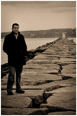 Self Portrait #1 (bkcasteel) Tags: ocean morning winter portrait blackandwhite bw usa lighthouse selfportrait seascape stone wall canon 50mm rocks alone cloudy coat maine canon350d lonely canondigitalrebel canonxt canonrebelxt atlanticocean canoneosdigitalrebelxt breakwater topaz rockland 50mmf18 canonef50mmf18ii niftyfifty topazbweffects bryancasteel