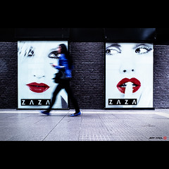 Ignorance (Jeff Krol) Tags: street city light red woman motion blur color wall walking twins eyes women fuji bricks streetphotography pedestrian lips billboard motionblur finepix fujifilm bliss zwolle ignorance x10 zaza dscf1698 jeffkrol fujix10 fujifilmfinepixx10