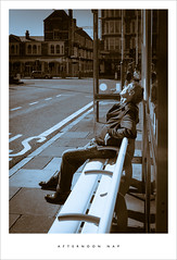 Afternoon nap (Parallax Corporation) Tags: sleeping blackandwhite sunshine pavement candid streetphotography busstop busshelter duotone roadside sunbathing southport towncentre