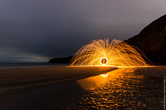 Spark. (Ollie Smalley Photography  Travelling) Tags: ocean sea orange black beach wool water wales canon reflections landscape fire photography wire long exposure cloudy cove sigma overcast ollie le 1020mm sparks shimmering headland smalley 550d