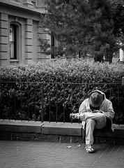 Sad Homeless Man (pillarsoflight) Tags: street blackandwhite bw plants white black building tree monochrome beauty hat oregon 35mm portland prime grey aperture nikon shoes waiting downtown sitting sad homeless gray khaki adobe pdx desaturated 18 bushes pnw lightroom d3300