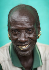 Senior Bana Man With Siwak Stick And Earrings Portrait Omo Valley Ethiopia (Eric Lafforgue) Tags: africa portrait people face smiling vertical picture earring tribal photograph blackpeople omovalley ethiopia tribe tribo amar amer frontview colorphoto nomadic omo thiopien etiopia onepersononly ethiopie etiopa humanface 1194 lookingatcamera manmen onemanonly  keyafer etiopija ethiopi indigenousculture  etiopien etipia  etiyopya  snnpr southernethiopia truepeople   exterioroutdoors  4549years 5054years omotic      southernnationsnationalitiesandpeoplesregion blackethnicity bannabana hamerhamarbannaameramarhammer ethiopianomovalley abyssiniahornofafrica siwakmiswaaksewakstick turquoisebluebackground ethio1194
