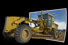 Grader Out Of Bounds (Robert Watson x) Tags: road usa tractor industry yellow america cat out photo 3d united transport perspective engine machine rail caterpillar illusion transportation states trick bnsf bulldozer outofbounds grader oob bounds of