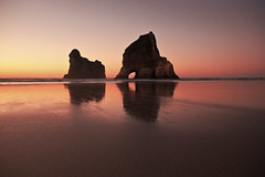 Wharariki Sunset glow (Tim Bow Photography) Tags: ocean pink light sunset newzealand storm color colour reflection beach water alone quiet purple tide nelson reflect nz british welsh washedup isolated svenska goldenbay landscapephotography whararikibeach timboss81 timbowphotography whararikibeachreflections