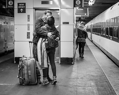 Penn Station (John St John Photography) Tags: newyorkcity people blackandwhite bw woman newyork man station train blackwhite kiss kissing platform streetphotography luggage goodbye embrace suitcase pennstation 7thavenue parting candidphotography peopleofnewyork
