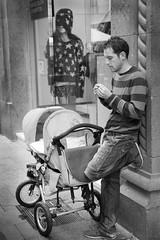 She's shopping (memories-in-motion) Tags: street city portrait people bw baby shopping iso800 mono cigarette father schaufenster smoker weiss schwarz kinderwagen vater zigarette einkaufen 65mm konzentration rauche canoneos5dmarkiii