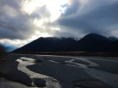 Dark Peaks (Steve Taylor (Photography)) Tags: newzealand sky cloud mountain cold contrast river glow stones nz southisland southernalps gravel braided