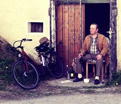 Thirsty (C_MC_FL) Tags: street door old portrait man hat bike bicycle comfortable vintage person photography austria sterreich chair sitting fotografie wine bottles alt fav20 retro hut alcohol sit drunken fujifilm mann alkohol tr fahrrad betrunken wein schnaps gemtlich sessel schnapps satisfied x10 flaschen sitzen softtones sitzend fav10 zufrieden strase