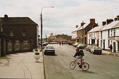 Market Square, Bagenalstown, Co. Carlow, 1991 (National Library of Ireland on The Commons) Tags: ireland cars ford church cycling nissan carina may bin guinness bicycles litter lorry orion toyota jetta 1991 signpost bluebird asa 16th thursday railings nineties 1990s corolla hurley camry romancatholic marketsquare fordescort carlow jewellers fordorion leinster toyotacorolla toyotacamry vwjetta telephoneboxes kitbag volkswagenjetta watchrepairs telephonekiosks nationallibraryofireland nissanbluebird bagenalstown fuls toyotacarina renault25 lawrencecollection asahouse lawrencephotographicproject federationforulsterlocalstudies federationoflocalhistorysocieties vzy907 bagenalstownhardwareltd bagenalstowntvcentre gaahelmet padraigjlaffan markivwjetta mark1vwjetta