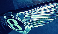 DSCF9538 (spreadthehappiness) Tags: lighting blue b shadow distortion abstract colour car closeup silver logo landscape 3d wings paint pattern curves feathers automotive highlights line depthoffield badge repetition straight shape tone bentley marque flyingb computerediting