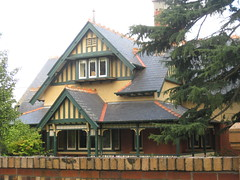 A Swiss Chalet Style Queen Anne Villa - Ballarat (raaen99) Tags: door city school trees windows chimney house building brick home window leaves architecture facade fence garden vent iron queenanne wroughtiron decoration australia victoria artnouveau doorway tiles brickwall villa weathervane slate railing verandah nouveau 1910s residence 20thcentury frontdoor lattice edwardian stucco gable federation ballarat halftimbered 1900s redbrick artsandcraftsmovement artsandcrafts fretwork teracotta reformist countryvictoria baywindow artscrafts latticework domesticarchitecture twentiethcentury sturtstreet sturtst brickfence queenannestyle federationstyle stpatrickscollege artscraftsmovement slaterooftiles edwardiana provincialvictoria chaletstyle returnverandah swisschaletstyle stuccoedbrick reformiststyle