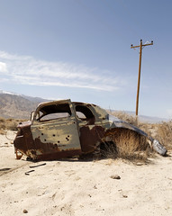 Desert Relic (Curtis Gregory Perry) Tags: auto old sky abandoned car clouds vintage sand rust automobile shot desert nevada mobil holes dyer rusted motor bullet coupe automvil xe automobil     samochd  kotse  otomobil   hi