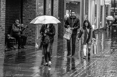 Serenading passers by in the Manchester rain. (steve.gombocz) Tags: street bw music rain manchester blackwhite noiretblanc zwartwit streetphotography olympus streetphoto streetmusic blacknwhite greyscale noirblanc whiteblack negroyblanco svarthvitt mustavalkoinen negroblanco neroebianco schwartzweiss olympuscamera sortoghvid svartochvitt schwartzundweiss svartoghvitt flickrbw flickrblackandwhite olympusm25mmf18 olympusem5mark2 czarnyibiaty flickrblackwhitephotos