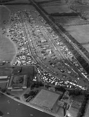 Aerial view of the Hoppings, 1964 (Tyne & Wear Archives & Museums) Tags: show road park door roof shadow people industry window glass festival stone wall buildings river handle daylight interesting construction traffic post unitedkingdom path seat pillar aerialview aerialviews bank vessel fair row vehicles doorway event entertainment transportation dome frame gathering archives land vegetation barrier rides unusual van festivities funfair development crowds newcastleupontyne fascinating digitalimage helterskelter aerialphotograph townmoor 1882 aerialphotographs socialhistory greatnorthroad exhibitionpark blackandwhitephotograph fairgroundrides northeastofengland june1964 thehoppings gosforthpark newcastletownmoor temperancefestival summerracemeeting 40acresofland