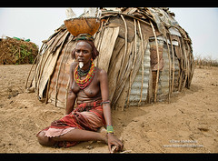 Dassanech woman in front of her hut in the Lower Omo Valley of Ethiopia (jitenshaman) Tags: poverty life africa travel black fur african traditional tribal hut hide destination omovalley jewelery tradition ethiopia tribe hyena ebony carry primitive ethiopian thirdworld omo pelt animalskin ethnicminority waterjug southomo dassanech worldlocations daasanach loweromo daasanech dassanach ormorate dasenuch hyenaskin