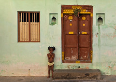 Little Girl With Hands Over The Mouth Posing In Front Of A House In Pondichery, India (Eric Lafforgue Photography) Tags: door travel shirtless people india house funnyface color colour green window girl horizontal children outside outdoors kid day child fulllength indoors greenhouse barefoot bracelet bunches bangle pigtails hindu atplay oneperson bindi pondicherry southindia colorimage pondichéry lookingatcamera indianpeople windowbar onegirlonly indianquarter puducherry formerfrenchcolony semidressed onechildonly unionterritoryofpondicherry oneyounggirlonly a702404 handoverthemouth