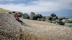 Fun with pebble avalanches (Kathrin & Stefan) Tags: ocean newzealand sky cloud beach nature rock fun bay outdoor slide pebble southisland tasmansea riverton foveauxstrait oraka colacbay kathrinmarks raka