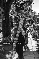 Take away crucifix (Barbara Oggero) Tags: street city urban italy woman lake christ cross religion jesus streetphotography crucifix capture orta viacrucis