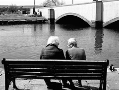 QuaysideCouple (Hodd1350) Tags: bridge bw water bench mono blackwhite couple sitting arches wb olympus dorset backs talking seated quayside wareham whiteblack oaps penf riverfrome zuikolens